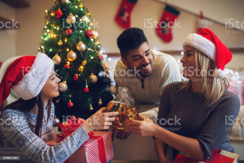 Happy playful lovely christmas friends with Santa hats and sweaters enjoying home for holidays. Drinking alcohol. stock photo
