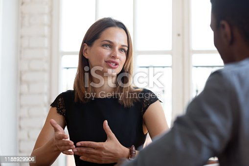 Head shot focus on happy pleasant young female financial advisor realtor lawyer explaining contract details to concentrated thoughtful african american male client at meeting in company office.