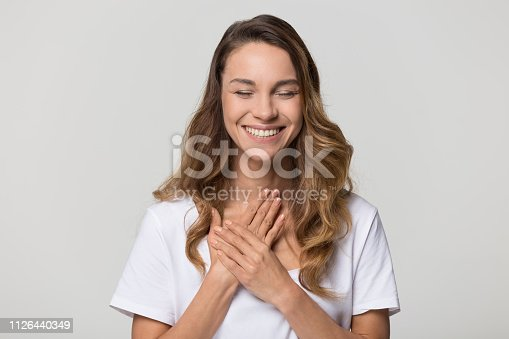 Happy pleased young woman thanking for care feel grateful holding hands on chest to heart isolated on white studio blank background, smiling sincere girl showing love heartfelt gratitude appreciation