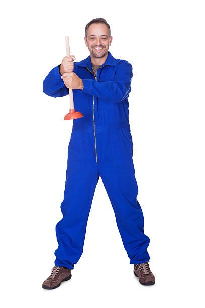 happy klempner holding saugglocke - jumpsuit blau stock-fotos und bilder
