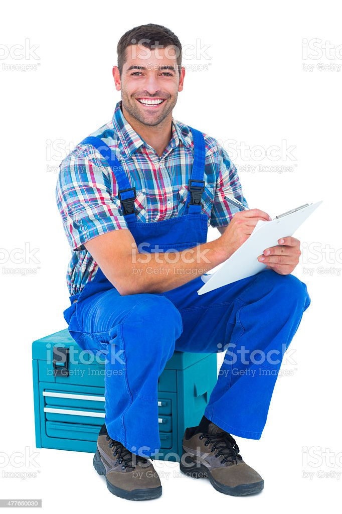 Happy plumber writing on clipboard stock photo