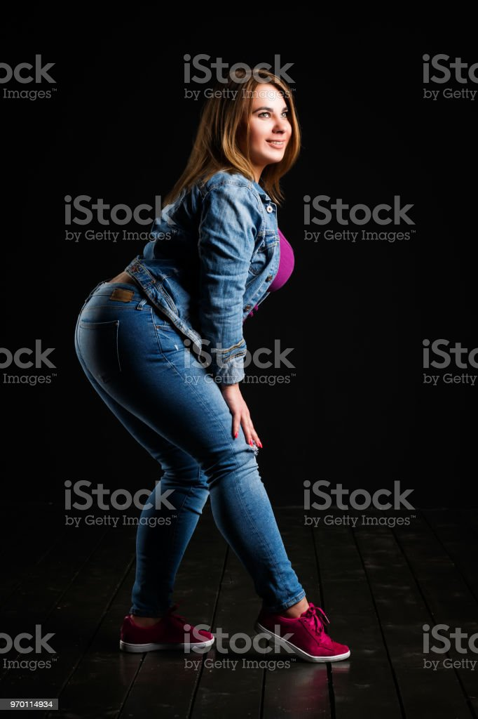 Happy plus size fashion model in blue jeans, fat woman on black studio background, overweight female body stock photo
