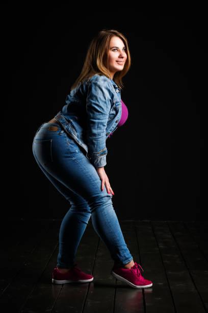 plus size mode-modell in blue jeans, dicke frau auf schwarzen studio-hintergrund, übergewichtige weibliche körper glücklich - damen sporthose übergröße stock-fotos und bilder