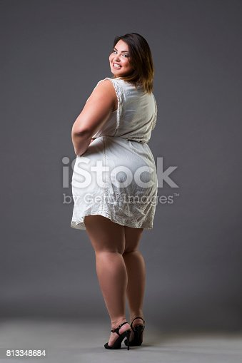 istock Happy plus size fashion model in casual clothes, fat woman on gray background, overweight female body 813348684