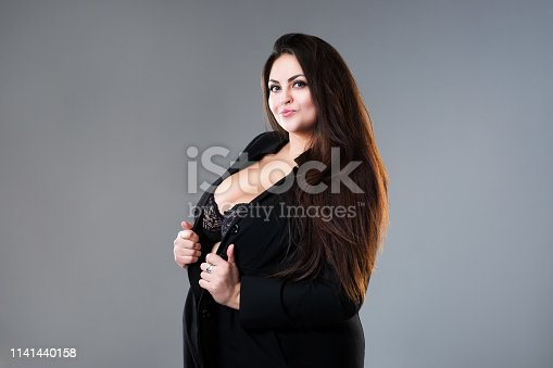 498310066istockphoto Happy plus size fashion model in sexy clothes, fat woman on gray studio background 1141440158