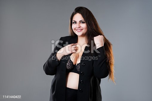 498310066istockphoto Happy plus size fashion model in sexy clothes, fat woman on gray studio background 1141440422