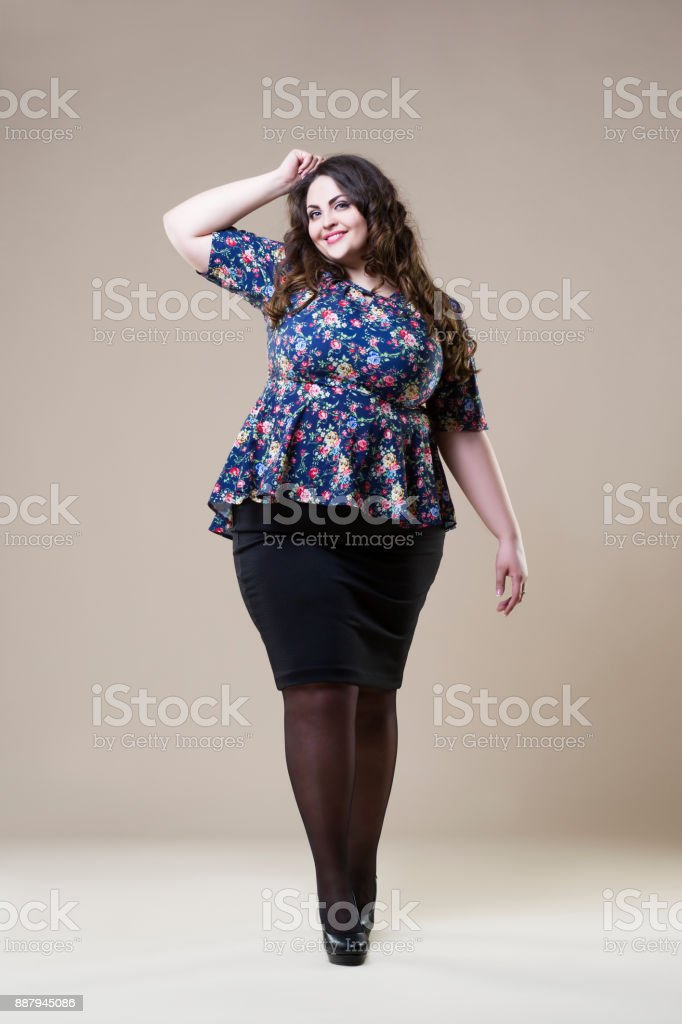 Happy plus size fashion model, sexy fat woman on beige background stock photo