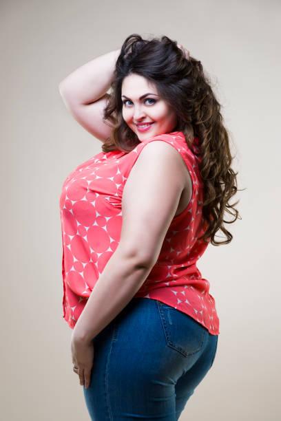 plus size mode-modell, sexy dicke frau auf beige hintergrund glücklich - damen jeans übergrößen stock-fotos und bilder