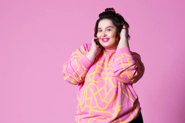 Happy plus size model in casual clothes, fat woman on pink background stock photo