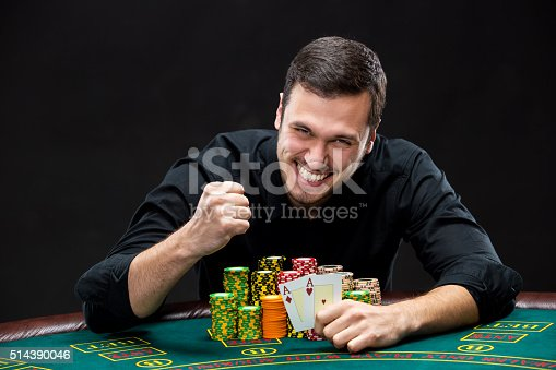 istock Happy poker player winning and holding a pair of aces 514390046