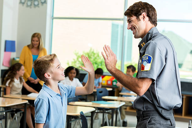 Happy police officer gives high five to student Mid adult Caucasian police officer smiles while giving a high five to elementary student after class safety presentation. The boy is wearing a school uniform. Students are studying in the background. police meeting stock pictures, royalty-free photos & images