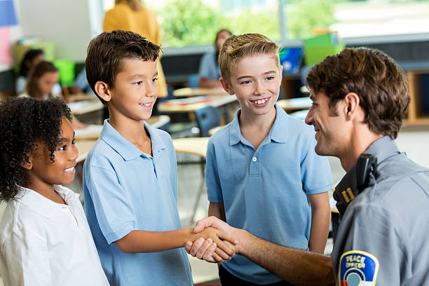 Happy police officer greets schoolchildren Friendly policeman shakes hands with private school students after giving a safety presentation. The diverse students are wearing school uniforms. police meeting stock pictures, royalty-free photos & images