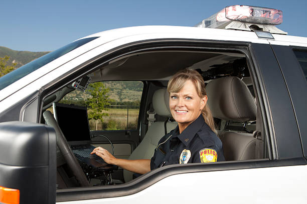 Happy Policewoman Driving Police Car on computer Happy Policewoman Driving Police Car on computer. This stock image has a horizontal composition. Arm Badge Create by me, Gold Chest Emblem Custom Ordered Generic border patrol stock pictures, royalty-free photos & images