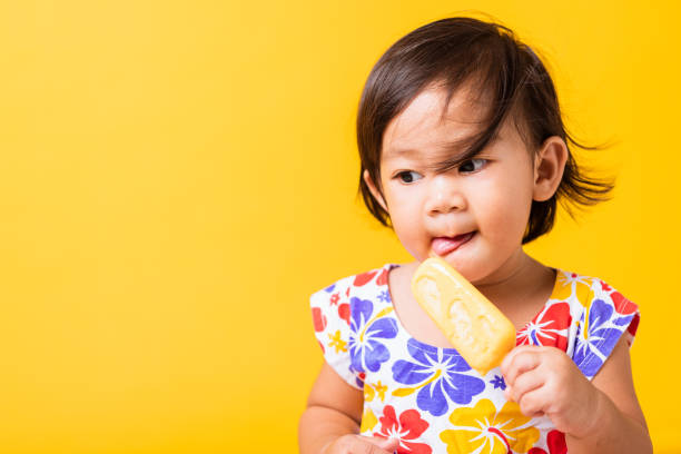 Happy portrait Asian baby or kid cute little girl attractive laugh smile wearing dick pattern shirt holds and eating sweet wooden ice cream, studio shot isolated on yellow background, summer concept Happy portrait Asian baby or kid cute little girl attractive laugh smile wearing dick pattern shirt holds and eating sweet wooden ice cream, studio shot isolated on yellow background, summer concept Dick stock pictures, royalty-free photos & images