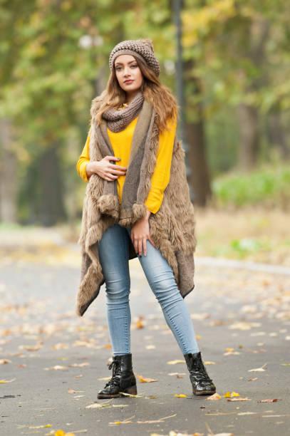 Happy Portrait-Mode einer schönen jungen kaukasischen Frau mit brauner Mütze und Schal und gelbem Pullover im Herbstpark, rot-grün-gelbe Dreier. Herbst, Saison und Menschen Konzept. Herbst-Lifestyle – Foto