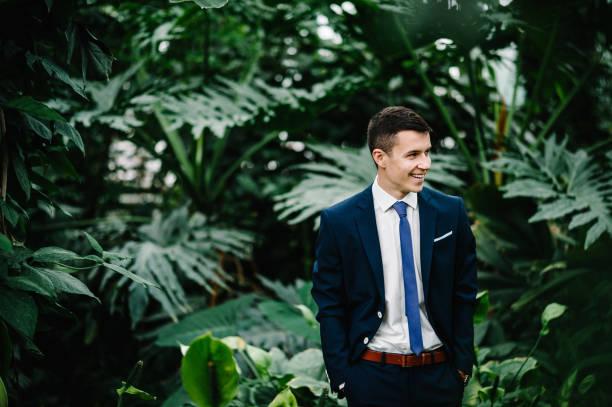glücklich porträt hübscher bräutigam hochzeitsanzug und krawatte steht auf dem hintergrund grün. der mensch steht im botanischen garten voller grün. - bräutigam anzug vintage stock-fotos und bilder
