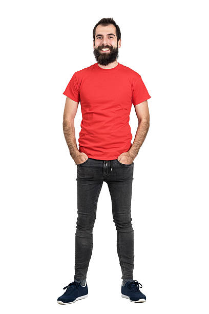 Happy positive bearded man in red t-shirt and tight jeans Happy positive friendly bearded man in red t-shirt and tight jeans laughing at camera. Full body length portrait isolated over white studio background. red shirt stock pictures, royalty-free photos & images