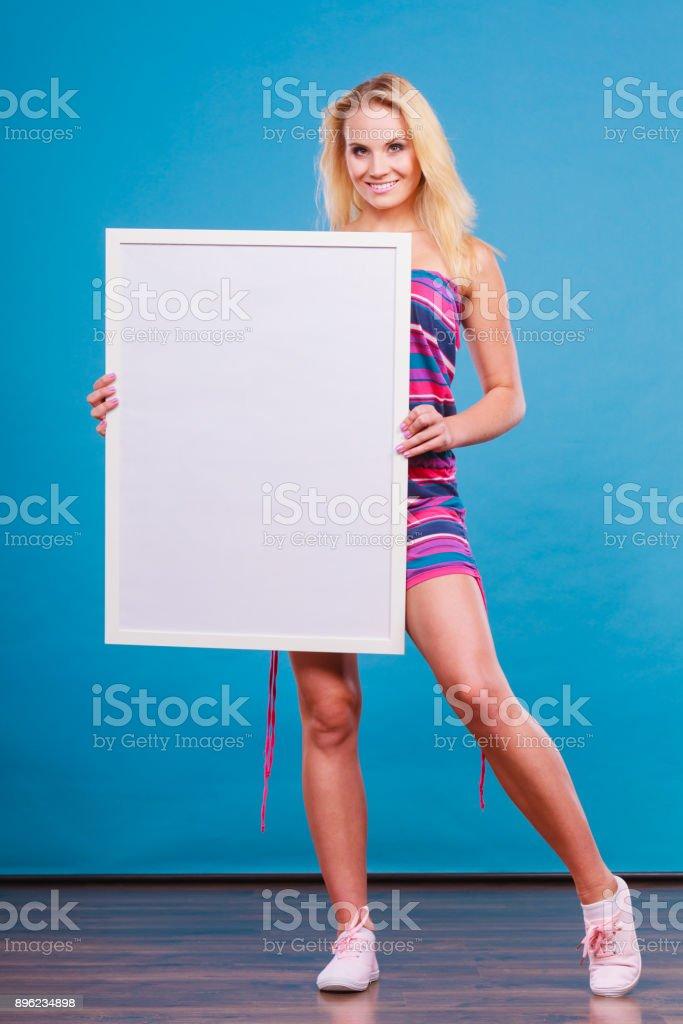 Feliz mulher loira positiva, segurando a placa branca em branco - foto de acervo