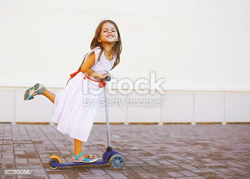 istock Happy positive child in dress on the scooter 522850567