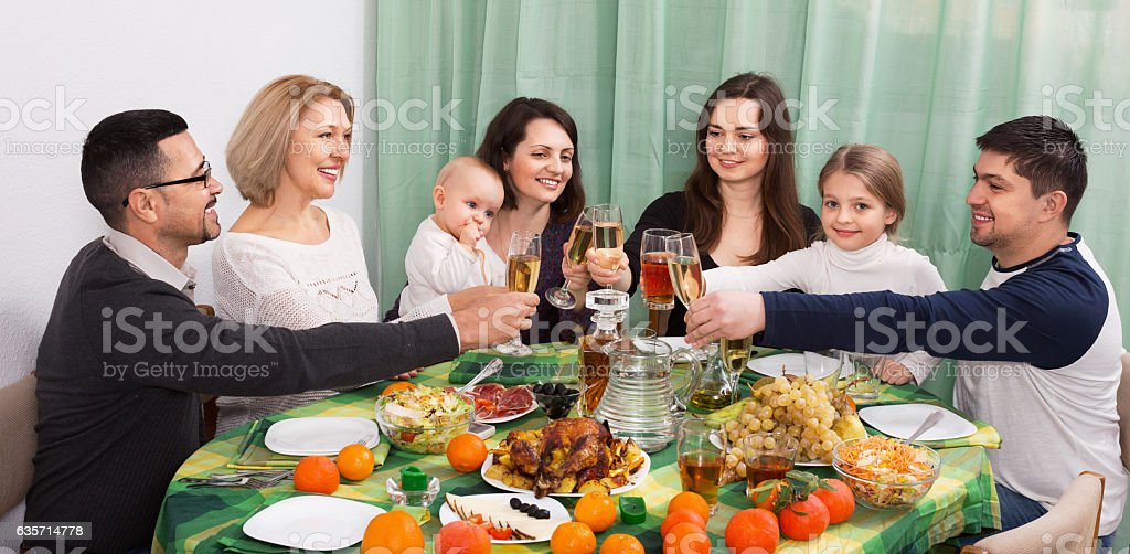 Happy positive multigenerational family sitting at holiday table royalty-free stock photo