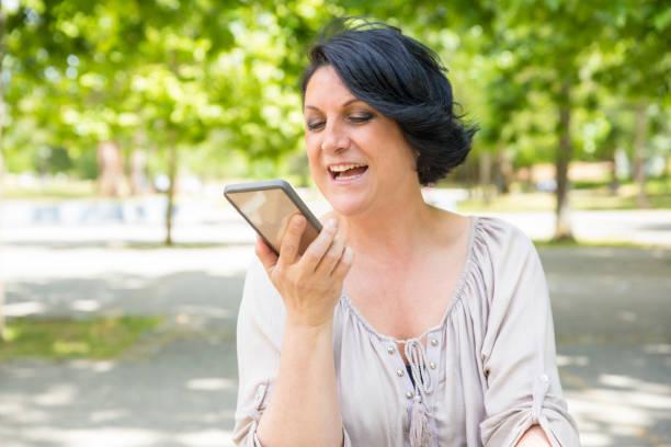 glücklich positive frau, die sprachnachricht aufnimmt - nachrichten video stock-fotos und bilder