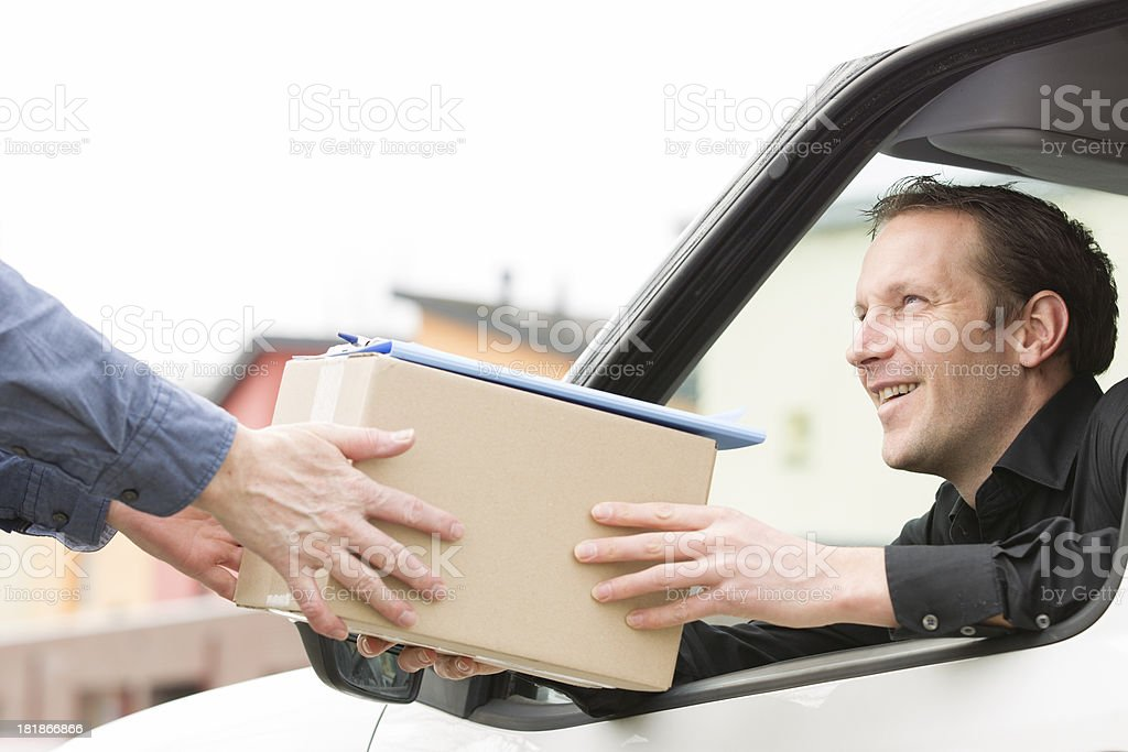 Happy postal delivery courier in a van delivering package royalty-free stock photo