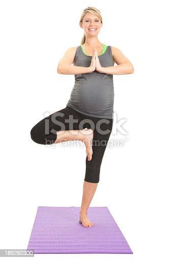 1071305850istockphoto Happy pregnant balancing in yoga pose 185262300