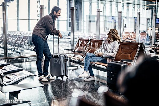 842907838 istock photo Happy pregnant communicating while waiting for their flight at departure area. 1151549215