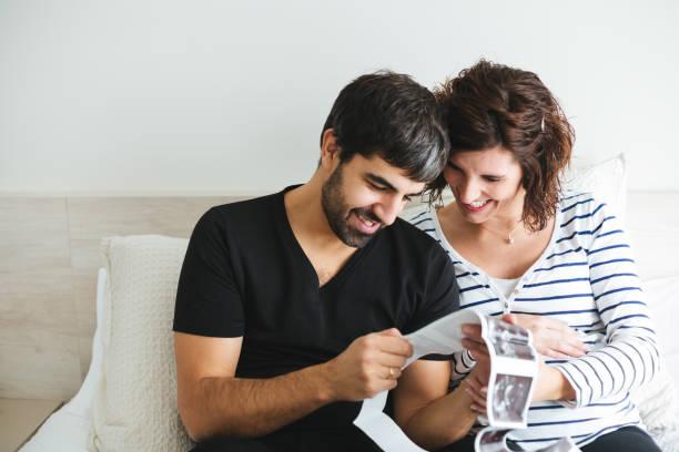 Glückliches, schwanges Paar mit Blick auf die Ultraschallbilder ihres Babys – Foto