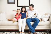 Happy pregnant family of three with dog spending quality time together at home