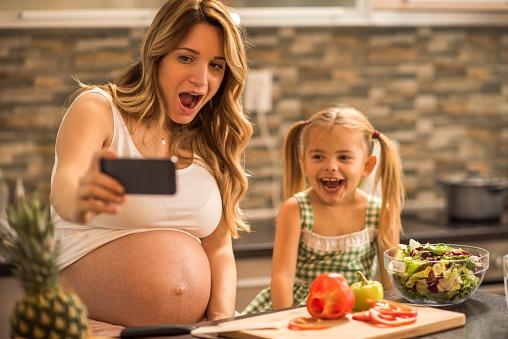 행복 한 임신 엄마와 딸이 부엌에서 휴대 전화와 함께 Selfie를 복용 2명에 대한 스톡 사진 및 기타 이미지