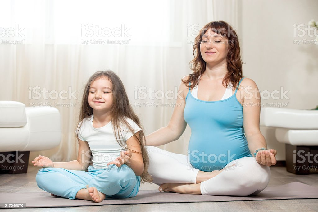 Happy pregnant mother and kid girl meditating together at home - foto de stock