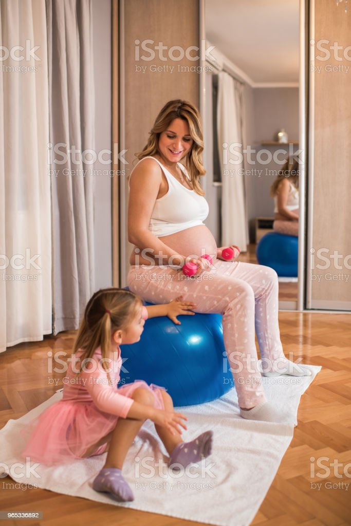 Happy pregnant mother exercising and talking to her daughter at home. zbiór zdjęć royalty-free