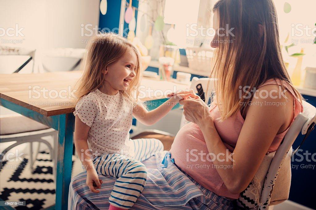Feliz Madre embarazada juegan con niño pequeño hija en casa - foto de stock