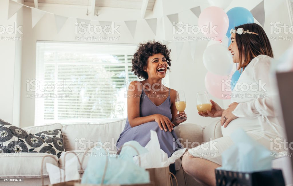 Happy pregnant woman and her friend at baby shower stock photo
