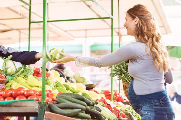 glücklich schwanger frau gesunde lebensmittel auf dem markt kaufen - latzhose für schwangere stock-fotos und bilder