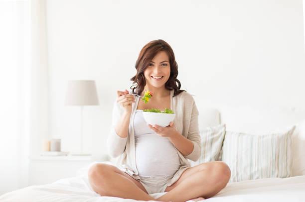 happy pregnant woman eating salad at home stock photo