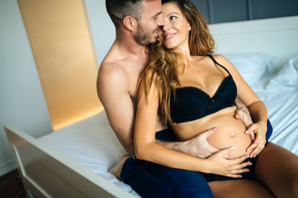glücklich schwanger frau mit mann im schlafzimmer genießen - sex sexuelle themen stock-fotos und bilder