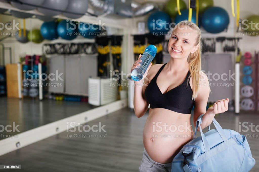 Gelukkig zwangere vrouw met tas en bidon op sportschool foto