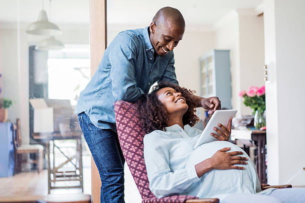 Happy pregnant woman looking at man in home stock photo
