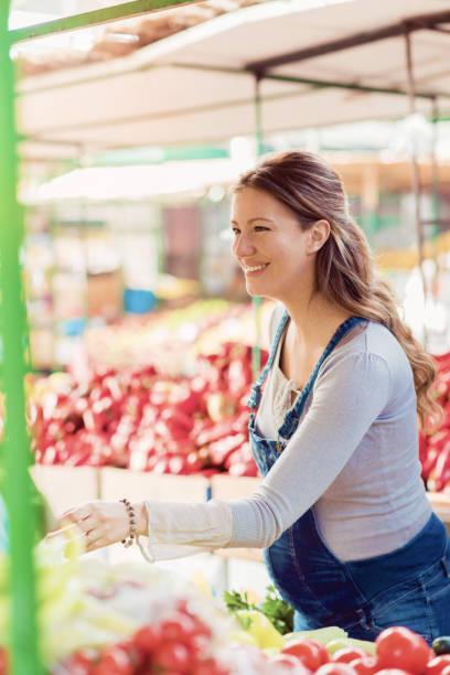 glücklich schwanger frau einkaufen auf dem bauernmarkt - latzhose für schwangere stock-fotos und bilder