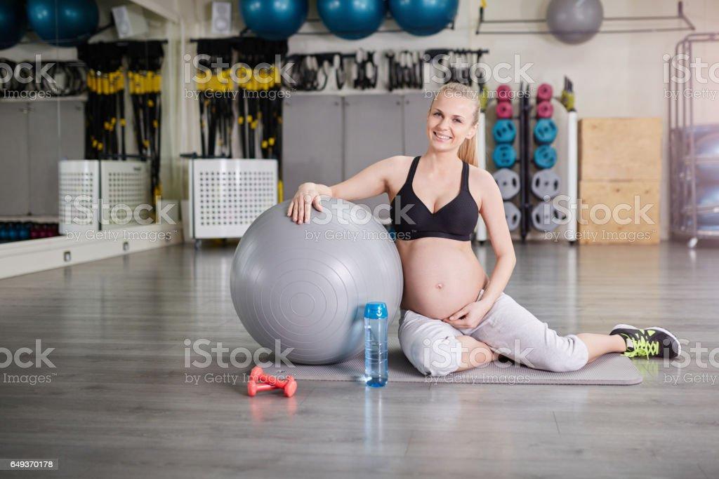 Gelukkig zwangere vrouw zit op sportschool met sport accessoires foto
