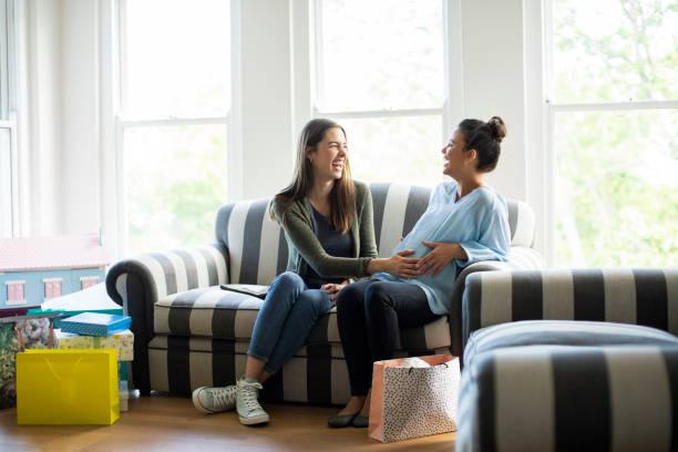 Feliz mujer embarazada sentada con amigo en el sofá - foto de stock