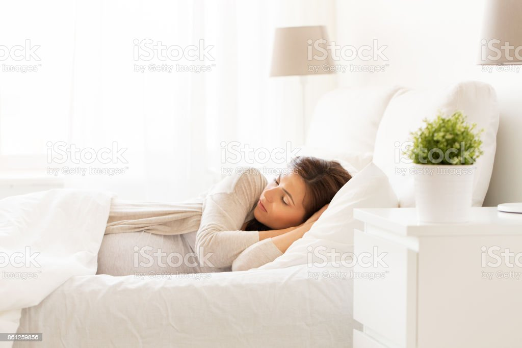 happy pregnant woman sleeping in bed at home royalty-free stock photo