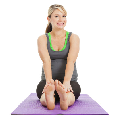 happy pregnant woman stretching out on yoga mat stock