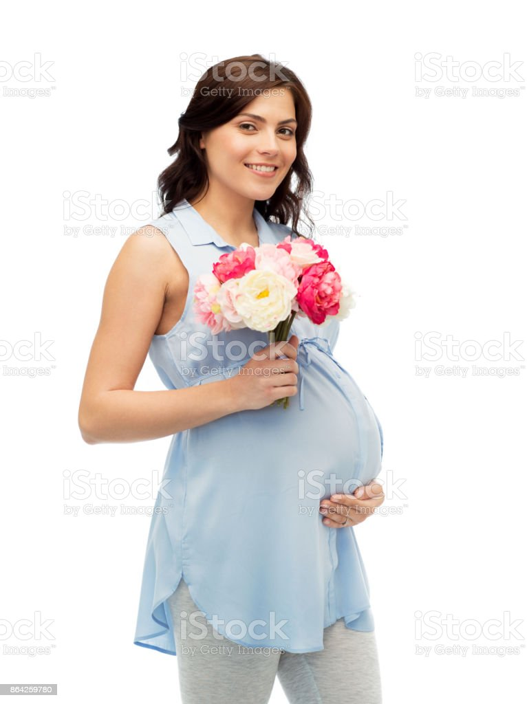 happy pregnant woman with flowers touching belly royalty-free stock photo
