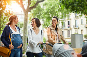 Happy pregnant woman talking to friends pushing baby strollers on sunny day