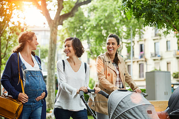 Happy pregnant woman with friends in park stock photo