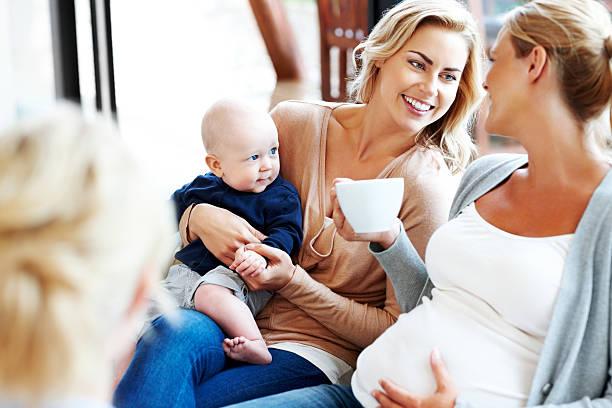 Feliz mujer embarazada con sus amigos relajante en su casa - foto de stock