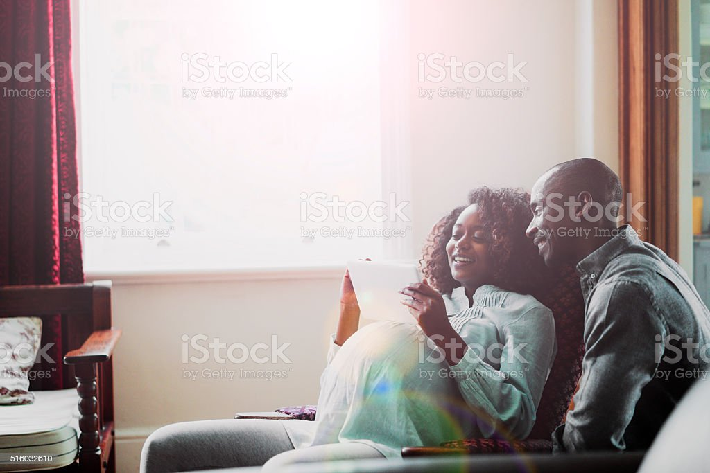 Happy pregnant woman with man using digital tablet at home stock photo